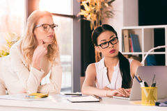 Pensive multiethnic businesswomen in formalwear looking at laptop at office. Young pensive multiethnic businesswomen in formalwear looking at laptop at office Stock Photography
