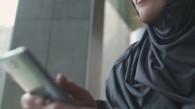 Pensive Muslim woman typing message on phone, making serious decision, closeup. Stock footage stock video