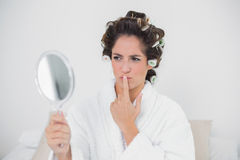 Pensive natural brunette looking at mirror Royalty Free Stock Images