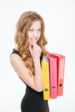 Pensive nervous pretty young businesswoman holding colorful folders and thinking Stock Photography