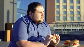 Pensive obese man eating burger, hesitating to start new life, weight loss. Stock photo stock photography