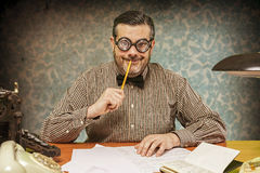 Pensive office employee with a pencil in his mouth looking up in Stock Image