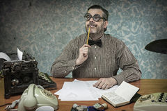 Pensive office employee with a pencil in his mouth looking up in Stock Photo