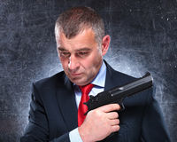 Pensive old assassin holding his gun stock image