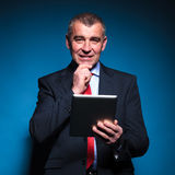 Pensive old business man reading on a tablet Stock Photography