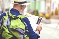 Pensive old male tourist searching for place of destination Stock Image