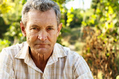 Pensive old man. Outdoors in summer garden Stock Photography