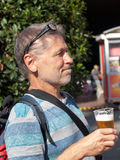 Pensive old man with beer. Pensive man drinking light beer royalty free stock image
