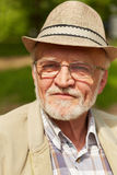 Pensive old man with hat and glasses Stock Image