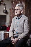 Pensive old man indoor Royalty Free Stock Image