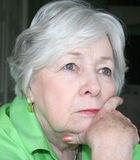 Pensive Older Woman in Color. A pensive older woman lost in thought royalty free stock photo