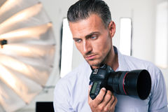 Pensive photographer holding camera. Portrait of a pensive photographer holding camera and looking at camera in studio Royalty Free Stock Photos