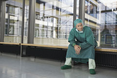 Pensive Physician Sitting In Hospital Corridor Royalty Free Stock Images