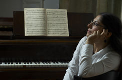 Pensive Piano Teacher Portrait. Pensive portrait of a piano teacher sitting in profile in front of a piano, with music open on the piano stand.  Teacher seated Royalty Free Stock Photos