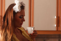 Pensive pin up girl drinking tea or coffee at home Royalty Free Stock Photography