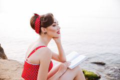 Pensive pin up girl sitting with book on the rock Stock Photos