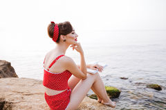 Pensive pin up girl sitting with book on the rock Stock Photo