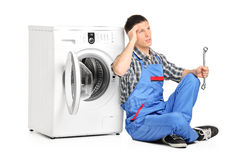 Pensive plumber fixing a washing machine Stock Photo