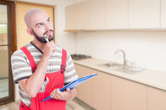 Pensive plumber in the kitchen. Holding clipboard with cheklist and copyspace area stock photography