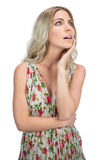 Pensive pretty blonde wearing flowered dress posing Royalty Free Stock Photos