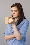 Pensive pretty brunette holding cup of coffee Royalty Free Stock Image