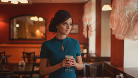 Pensive pretty girl in classic elegant dress standing at the cafe going to drink coffee. Royalty Free Stock Photography