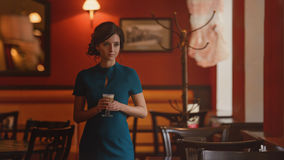 Pensive pretty girl in classic elegant dress standing at the cafe going to drink coffee. Royalty Free Stock Images