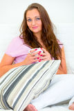 Pensive pretty woman with cup of coffee on sofa Stock Image