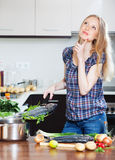 Pensive pretty woman with raw  fish in frying pan Royalty Free Stock Images