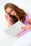 Pensive pretty woman reading newspaper on sofa Stock Image