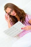 Pensive pretty woman reading newspaper on sofa Stock Image