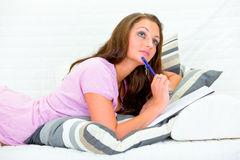 Pensive pretty woman on sofa writing in notebook Stock Images
