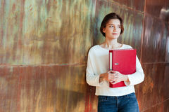 Pensive pretty young woman holding red ring binder folder. Pensive pretty young woman standing in office and holding red ring binder folder Royalty Free Stock Image