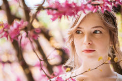 Pensive pretty young woman in spring garden Royalty Free Stock Photography