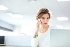 Pensive pretty young woman talking on cell phone in office Stock Photos