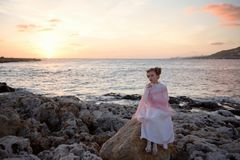 Pensive sad princess girl in a pink dress and a diadem is sitting on a rock on the ocean seashore and meets the dawn of the sunris. Pensive princess in a pink Royalty Free Stock Photos