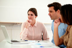 Pensive professional group looking at laptop royalty free stock images