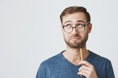 Pensive professor with beard in spectacles and casual clothes, has clever expression, looks thoughtfully aside, holds. Horizontal shot of pensive university stock photos