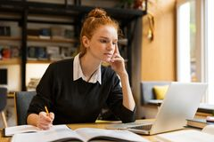 Pensive red haired teenage girl using laptop computer royalty free stock photography