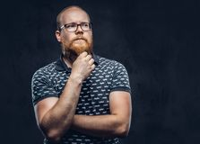 Pensive redhead bearded male in glasses dressed in a t-shirt posing with a hand on chin. Isolated on dark textured royalty free stock image