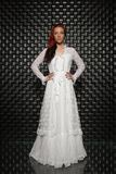 Pensive redhead lady posing in studio. On black background dressed in white long dress stock images