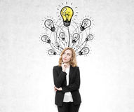 Pensive redhead woman near light bulb sketches Stock Photography