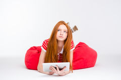 Pensive redhead young woman using tablet Stock Photos