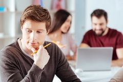 Pensive reflecting guy confronting problem. Serious issue. Meditative pleasant young guy gazing aside while touching chin and holding pencil Royalty Free Stock Image