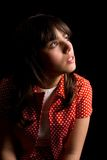 Pensive or sad brunette girl over dark background Stock Image