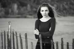 Pensive sad lonely Caucasian young beautiful woman with messy long hair on windy day. Black and white portrait of pensive sad lonely Caucasian young beautiful Royalty Free Stock Image
