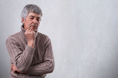 Pensive sad mature man holding his hand under his chin looking down with unhappy expression thinking about something. Thoughtful e Royalty Free Stock Images