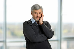 Pensive sad mature man. Upset senior man standing on blurred background. Lost in thoughts royalty free stock photo