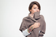 Pensive sad woman with tatoo hiding lipd behind knitted jacket Royalty Free Stock Photography