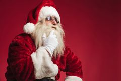 Pensive santa claus touching beard and chin Royalty Free Stock Images